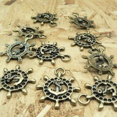 Take a look at these ship wheel anchor helm charms...  You will receive 10 pieces.  These charms are made from a zinc alloy metal which is lead