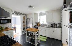 shelf next to fridge, wide tile floor, stainless/butcher block counters