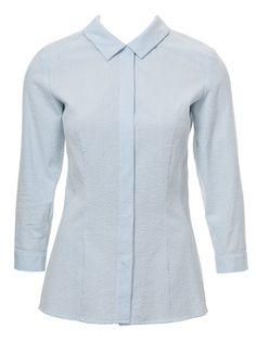 Die stylische, cleane Bluse mit verdeckter Knopfleiste wird jetzt hochgeschlossen getragen.