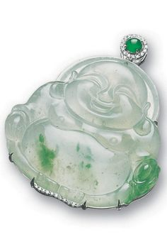 *ICY JADEITE 'BUDDHA' AND DIAMOND PENDANT The highly translucent jadeite material of light celadon colour carved as a Buddha suffused with green splashes, surmounted by a rounded jadeite cabochon of bright emerald green colour, decorated with brilliant-cut diamonds, mounted in 18 karat white gold.