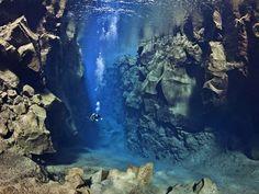 Mergulhador nada entre placas tectônicas.  Diver swims between tectonic plates.