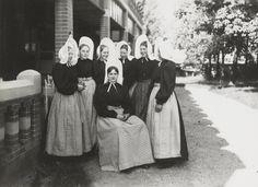 Groep jonge vrouwen in Huizer streekdracht. Over een zwarte ondermuts dragen ze de 'isabee': een muts met een hoog opstaande gesteven voorstrook. Onderin de rokken en schorten is een aantal horizontale oprijgsels gemaakt, de zogenaamde 'bessels'. 1918-1941 vanAgtmaal #NoordHolland #Huizen