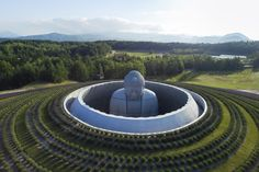 Tadao Ando: Makomanai Takino Cemetery, Sapporo 2015. Before the temple was completed, the 44-foot-tall Buddha sculpture stood alone in a field for 15 years. The resulting temple envelops the statue, leaving only the top of its head visible from outside the hill, planted with 150,000 lavenders.