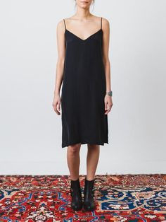 Luxurious black slip dress with a sleek silhouette and thin spaghetti straps. Features slits on both sides at the bottom hem. - Slightly dipped neckline - Pull over style - 100% Silk - Made in Canada
