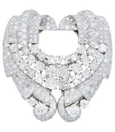 AN ART DECO DIAMOND AND PLATINUM DOUBLE-CLIP BROOCH, CHARLTON & CO., CIRCA 1935. Of odeonesque inspiration, the twin plaques with geometric curved ribbon scrolls and sashes decorated by thirty old mine-cut diamonds and smaller diamonds, mounted in platinum, with brooch fitting, signed Charlton.