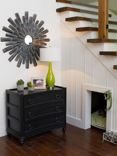 The area adjacent to the stairs is accessorized with this three-drawer console and some well coordinated accent pieces.