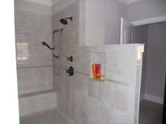 another angle of walk-in doorless shower. bench at end and shampoo niche