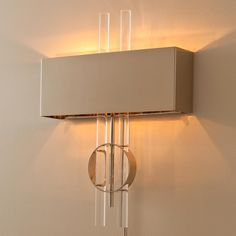 Graphic Interpretations Wall Sconce Two straight acrylic rods intersect a shiny nickel circle, layered with a rectangular nickel metal shade creating contemporary graphic art for the wall. Large enough for vaulted spaces but narrow enough for hallways!