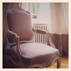 beautifully upholstered chair and also linen curtains in background