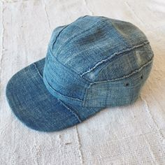 All of the texture of the beautifully crafted West African textiles comes through in this 5 panel camper hat. Beautifully distressed handwoven, hand dyed, and hand sewn vintage indigo with hand sewn seam ridges. Adjustable leather strap w/ antiqued brass slider and grommets.
