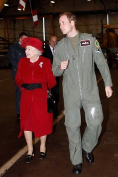 Queen Elizabeth II is escorted by her grandson Prince William during a visit to RAF Valley where Prince William is stationed as a search and rescue helicopter pilot