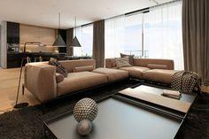 salon taupe contemporain avec grand canapé d'angle, salle à manger et cuisine assortis