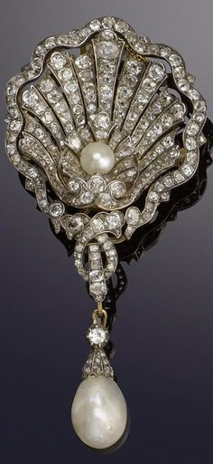 A late 19th century diamond and pearl shell brooch circa 1880. The large scallop shell pierced and set with a bouton pearl and old brilliant-cut diamonds suspending a pearl old brilliant and rose-cut diamond pendant diamonds approximately 5.90 carats total pearls untested length 9.0cm.