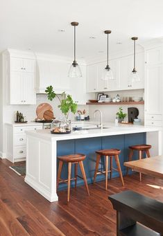 Three glass dome lanterns hang over a blue and white two-tone peninsula seating three wood tractor stools facing a stainless steel dual sink with a satin nickel gooseneck faucet in a beautiful u-shaped kitchen. Orisi Panos Interiors