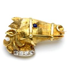 This beautiful estate brooch showcases a horse head design rendered in bright 18-karat yellow gold. A single blue sapphire eye is accented by a collar adorned with four white diamonds on this pin. Pre