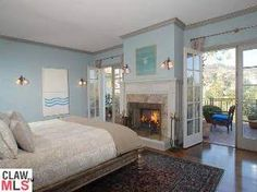 love the fireplace, doors leading to the balcony, shade of blue for the walls and the oriental rug over hardwood flooring.
