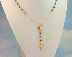 This is a beautiful multi layer Rosary Gemstone necklace made of 3mm Genuine Garnet gemstones with Blue Topaz on 24k gold verneil. This necklace measures 16 to 18, 18 to 20 or a 20 to 22 length with a 2 drop that has a small 15mm 18kt gold filled gold Italian crucifix cross pendant. Necklace comes with a gold filled toggle in back. *Model is wearing a 16-18 length.  Garnet is a stone of high vitality & energy, & lends vitality, strength, & sensuality. Given as a gift, garnet symbolizes true…