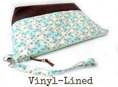 A stylish large Geometric print clutch bag in shades of jade and cocoa brown, perfect for holding everything you need from day to day and easily carried and shown off using the detachable wrist strap. Makes for an ideal makeup bag or a bag to carry your crafts, knitting supplies or to store your toiletries when traveling.