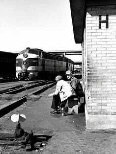 """September, 1952:  """"The oil lantern at the feet of the guy on the left and the Kromer cap on the guy on the right tell us that these are working railroaders waiting for something--the arrival of a train, the time for them to report for duty, something. They're in the vast complex of yard tracks that, in the 1950s, supported the huge Cincinnati Union Terminal. But the station, most of the yards, and probably these two railroaders aren't there any more."""""""