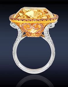 Fancy Intense Yellow Diamond Solitaire with pink and white diamonds set in platinum and 18K gold.  Jacob and Co.