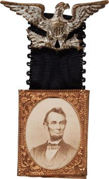 "Abraham Lincoln: Large Gem Albumen Mourning Badge. The black ribbon on this badge indicates it was used at the time of Lincoln's assassination. The copper frame is the large 1"" x 1 1/4"" size. The eagle retains most of its original silvered and stickpin attachment. It is a very clean example and quite scarce."