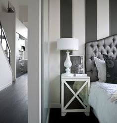 Chic bedroom design with white & charcoal gray striped walls, pewter gray silk tufted headboard, white milk glass lamp, white mirrored nightstand chest and black silk damask pillows.