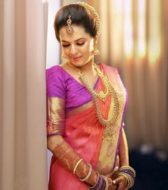 South Indian bride. Gold Indian bridal jewelry.Temple jewelry. Jhumkis.Pink and purple silk kanchipuram sari.Braid with fresh jasmine flowers. Tamil bride. Telugu bride. Kannada bride. Hindu bride. Malayalee bride.Kerala bride.South Indian wedding.
