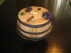 """Wine Barrel Cake:  two layer 9.5"""" rounds, two shades of fondant to create the wood effect, gumpaste leaves and stems, fondant grapes, fondant corks, and fondant corkscrew painted with silver pearl dust."""