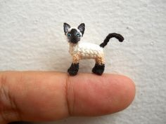 Miniature crocheted animal - The Siamese cat is made of embroidery threads, micro plastic eyes and stuffed by polyfil.  Size: Aprox. 1 inch ( 25 mm) long and 0.8 inch (20 mm) tall.  Perfect for cat lovers, any DOLLHOUSE animal display, mini cat collection...  + Each item is individually hand made so it may vary slightly from the photos. + For more mini tiny crocheted cats, please see the section link https://www.etsy.com/shop/SuAmi?section_id=11064691 or back to Suami...