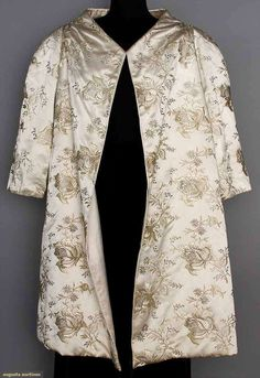 "PATOU COUTURE EVENING COAT, 1950s. Ivory satin w/ embroidered roses in white floss & metallic silver threads, collarless, 3/4 sleeves, open front, white satin lining, label ""Jean Patou Paris"", inked tape below ""77856"". Front"