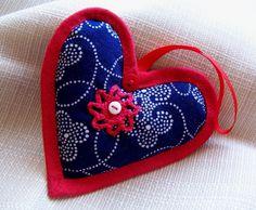 Modrotiskové srdce Šitá ozdobička z modrotisku ve tvaru srdíčka, s červeným knoflíčkem a krajkovou aplikací ve tvaru kytičky s bílým knoflíčkem, obšita červeným šikmým proužkem. Červená stužka k zavěšení. Velikost ozdobičky 8 cm.