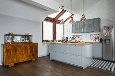 W salonie zastosowano wiszące lampy w industrialnym stylu i stylowy stary…