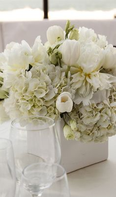 The tables will feature three square vases with the center vase filled with cream hydrangeas, ivory lisianthus, white tulips, and soft green lambs ear and the outer two vases with cream hydrangeas and lambs ear as well as scattered clear glass votives.