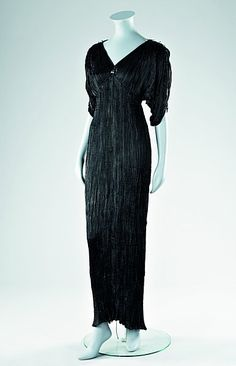 A Mariano Fortuny black silk Delphos gown, circa 1920-30, unlabelled, with black cords criss-crossing over the breast, elbow length curved sleeves, edged with lapiz-blue Murano glass beads