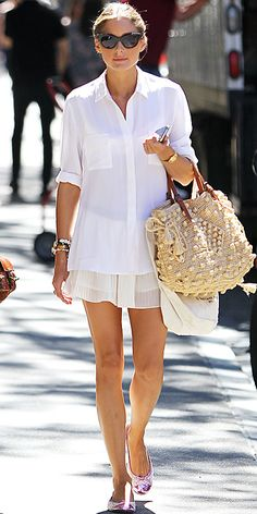 Olivia wore a a cuffed button-down and pleated skirt. Black shades, a woven tote, stacked bracelets and ballet flats completed the look.