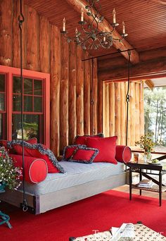 Enormously Appealing Lakeside Summer Cottage   Traditional Home -- Breezy and Inviting Porch -- A bed swing on the porch is an irresistible napping spot. The area's red palette reflects the metal roof above, which was treated to create a rust finish.