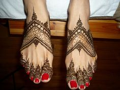 Mehendi on feet with bright red painted toes! I know some monsters who would love this!