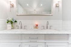 Gorgeous master bathroom features upper walls painted pale gray, Benjamin Moore Stonington Gray, and bottom part of walls clad in white subway tiles lined with a white dual topped with gray and white quartzite fitted with white porcelain sinks and gooseneck faucets placed under a full length beveled mirror.