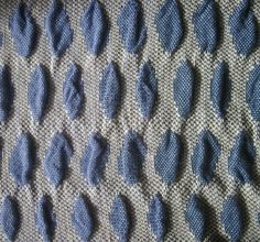 by Bonnie Inouye...My latest double weave was part of a warp done in mid-October. I washed it recently and took photos yesterday. The background is a single layer of cloth (twill) and the blue shapes are two layers of plain weave. The bottom layer has a shrinking weft and the top layer does not shrink, so it puckers. Both warps are cotton, 8/2 and 10/2. One weft is high-twist, very fine Lyocell (Tencel) and the other weft is a two-ply rayon/cotton which is thicker than the warp.