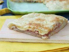 La pizza parigina è un classico delle rosticcerie italiane: base di pizza, copertura di sfoglia e ripieno prosciutto e formaggio. Buonissima e veloce.