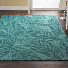 Aqua Leaves Indoor Outdoor Rug Large leaves outlined in teal on aqua offer high fashion color in an easy care area rug for indoor or outdoor use. Large loops are soft underfoot and durable for casual living. 100% Polypropylene.