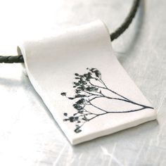 Clay Pendant Natural Plant Impression - Hand-sculpted Clay Pendant with Black and White Acrylic Finish.  via Etsy.