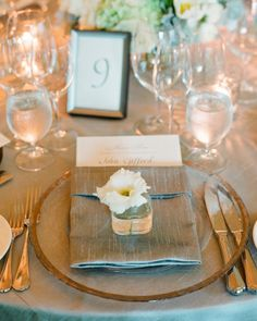A simple white bloom in a tiny glass vase was placed at each guests' seat for them to take home