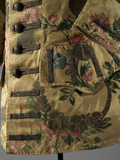 Detail Boy's coat, Italian, circa 1715 - 1750, Silk-brocaded lampas with silver filé . Bizarre silks are a style of figured silk fabrics popular in Europe in the late 17th and early 18th centuries. Bizarre silks are characterized by large-scale, asymmetrical patterns featuring geometrical shapes and stylized leaves and flowers, influenced by a wave of Asian textiles and decorative objects reaching the European market in these decades. Royal Ontario Museum.