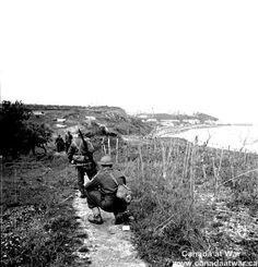 """Ortona - Company  B"""" of the Seaforth Highlanders moving along a mined coastal path December 21st, 1943. Ortona can be seen in the distance."""