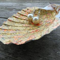 Have some shells laying around that you don't know what to do with? Check out this easy DIY and make a gold shell catchall with pearl feet!
