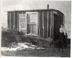 Carrie Ingalls standing outside her tiny shanty in South Dakota