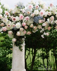 This dreamy floral arch featured pink and blue blooms that perfectly complemented the manicured garden #wedding #ceremony setting! | Photography By: Mango Studios | WedLuxe Magazine | #wedding #luxury #weddinginspiration #luxurywedding #floral #floralarch #vows #rose