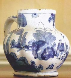 "A Rare London Delftware Blue and White Dry Jug Jar, 1690, painted on the front with a scroll-edged label suspending floral garlands and inscribed V APOSTOL above a fleur-de-lys and the date 1690. Height 6.75 in. Literature: Louis L. Lipski and Michael Archer, ""Dated English DElftware"", p. 384, no. 1658D (listed but not illustrated)"