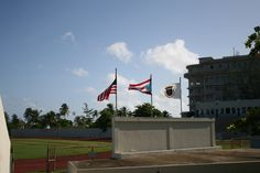 9. Museo del Deporte. (Domingo, 8:42 am) Podemos encontrar que el color azul de la bandera puertorriqueña sí es el correcto, azul celeste. A pesar de esto, por el resto de aspectos no se sigue con el protocolo, porque están izadas en el fin de semana, y además no debería estar presente la de Estados Unidos, porque Puerto Rico sí tiene autonomía deportiva, y se trata de una institución de dicho ámbito, por lo que con la de Puerto Rico y la de San Juan bastaría.